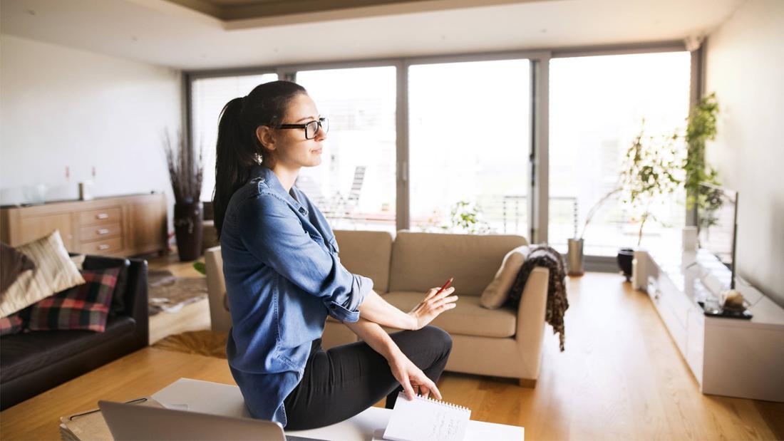 Eine Frau, die auf einem Tisch im Wohnzimmer sitzt und ein Notizbuch in der Hand hält, in welches sie mit einem Stift, den sie in der Hand hält, schon etwas herein geschrieben hat.