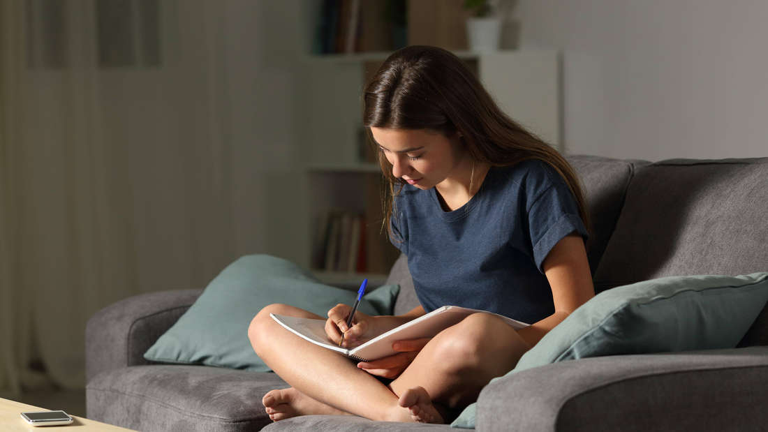 Eine Frau, die im Lotussitz auf einer grauen Couch sitzt und in ein Notizbuch oder einen Block schreibt. Vor ihr auf dem Tisch liegt ein Handy.