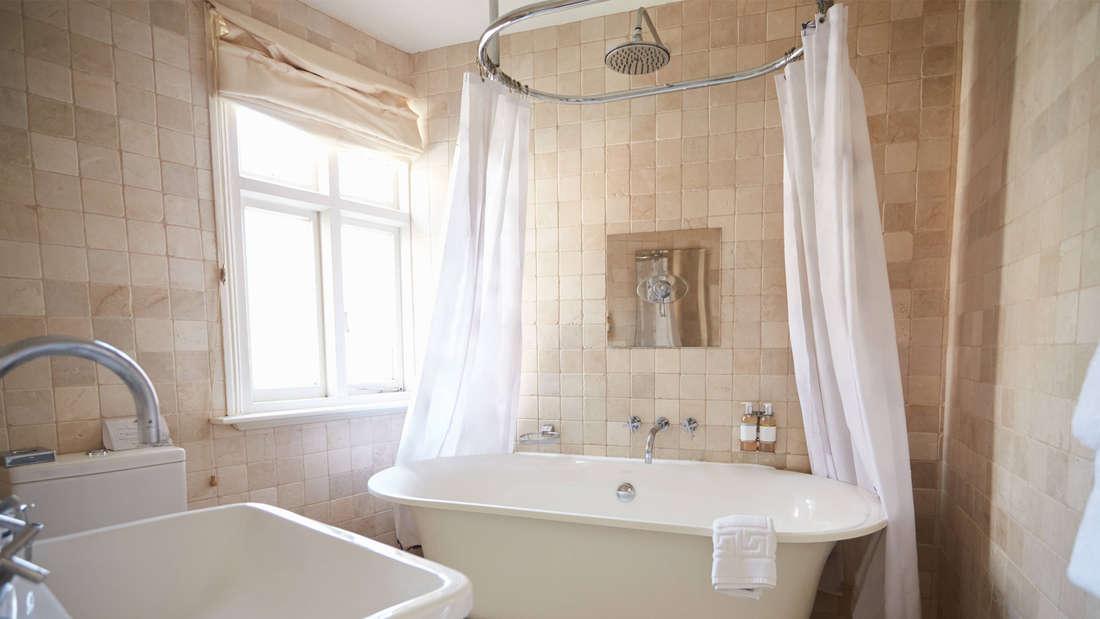 Ein Badezimmer, in dem eine große weiße Badewanne mit Duschvorhang steht. Daneben ist ein Fenster, durch das Licht strömt.