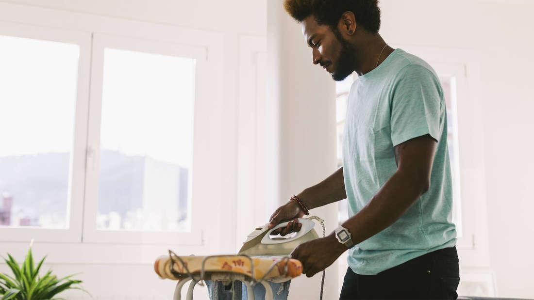Ein Schwarzer Mann, der in einem hellen Zimmer Klamotten auf einem gelben Bügelbrett bügelt.