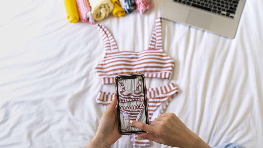 Eine Person, die ein Foto von einem Bikini macht, der auf einem Bett liegt. Am oberen Rande des Bildes sind mehr Klamotten und ein Laptop zu sehen.