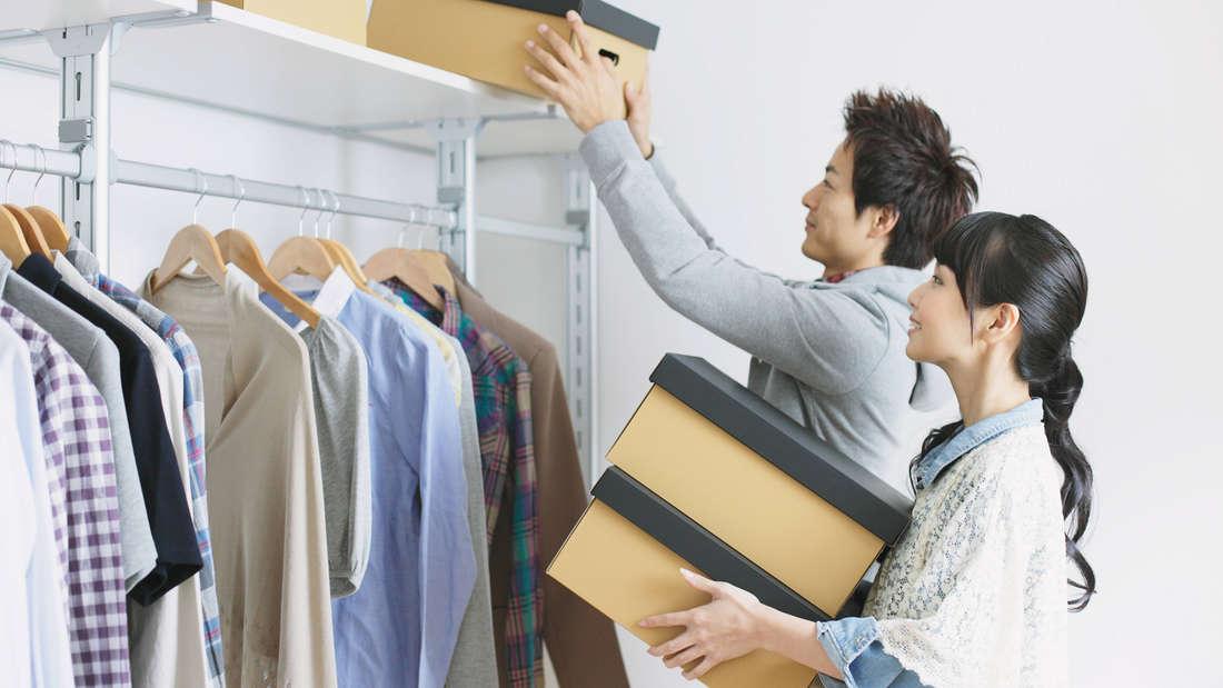 Eine Frau und ein Mann asiatischer Abstimmung räumen Kisten in das obere Regal eines Kleiderschranks. Beide lächeln dabei.