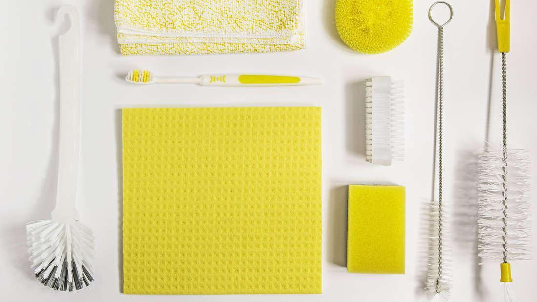 Eine weiße Toilettenbürste, ein gelbweißes Tuch, eine gelbweiße Zahnbürste, ein gelbes Putztuch, ein gelber Schwamm, eine Nagelbürste, ein gelber Topfschwamm und zwei gelbweiße Flaschenbürsten. Alles ist ästhetisch ansprechend nebeneinander aufgelistet.
