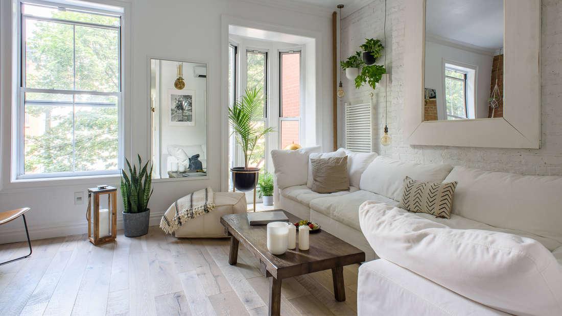 Ein ästhetisch ansprechend eingerichtetes Wohnzimmer mit weißer Couch, Hockern, Holztisch, vielen Pflanzen und zwei Spiegeln.