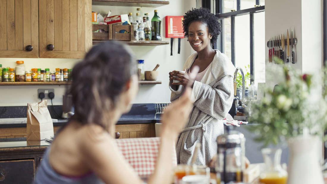 Zwei Frauen, die gemeinsam in einer Küche, die in Holztönen gehalten ist, frühstücken. Eine Schwarze Frau trägt einen Bademantel und hält einen Kaffee in der Hand, während sie die andere Frau anlächelt. Auf dem Tisch stehen Orangensaft und Blumen.