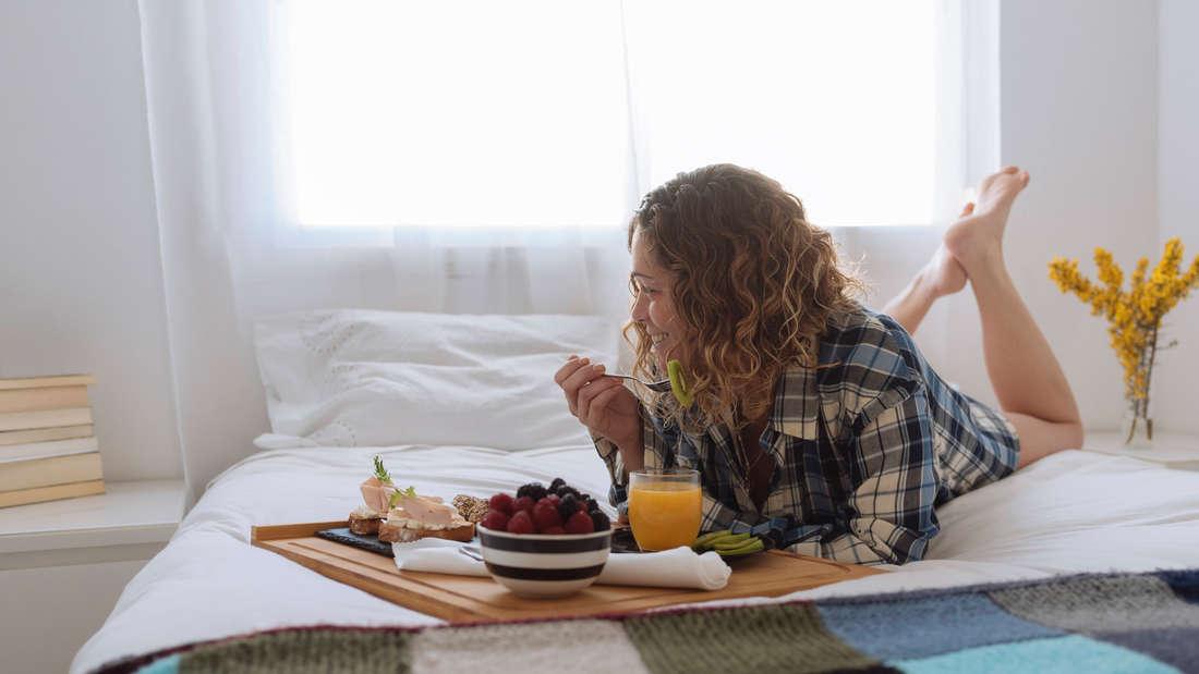 Eine Frau mit lockigen Haaren liegt auf einem Bett und lächelt, während sie mit einer Gabel eine Kiwi isst. Auf einem Tablett vor ihr stehen eine Schüssel mit Früchten, Orangensaft und Brote, sowie Kiwischeiben.