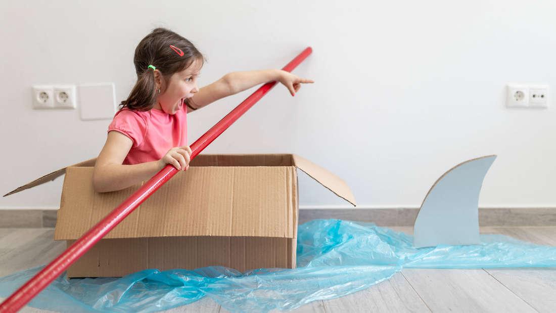 Ein Kind, das ruft und in einem Karton sitzt und einen roten Stiel als Segel benutzt. Auf dem Bild wurde blaue Folie ausgestreckt, die aussehen soll wie Wasser. Außerdem klebt auf dem Boden eine Haiflosse aus Karton.