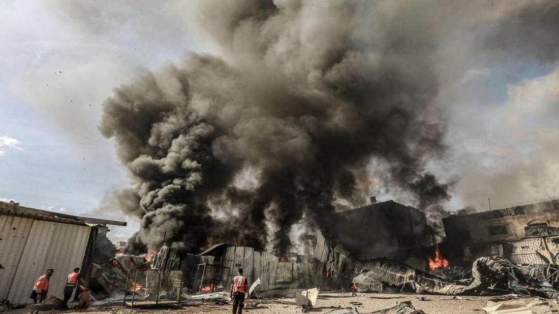 Rauch steigt auf, während Mitglieder der palästinensischen Zivilverteidigung in Gaza-Stadt versuchen, das Feuer in einer Schaumstofffabrik zu löschen, nachdem diese von israelischen Artilleriegranaten getroffen worden ist.