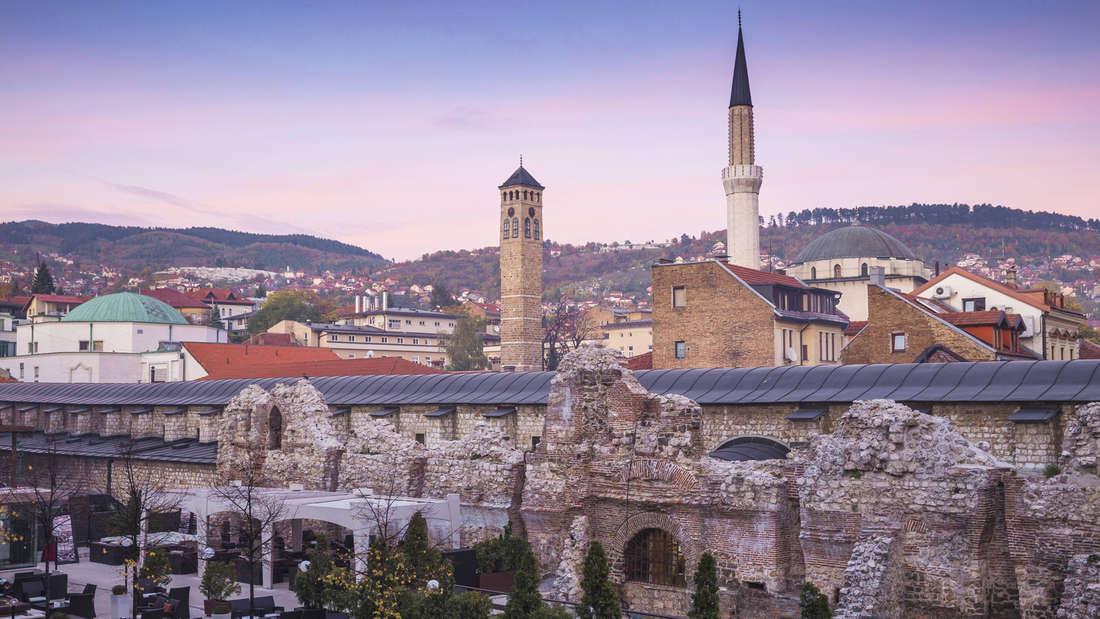 Die Altstadt Sarajevo mit Mauer, verschiedenen Gebäuden und Bergen im Hintergrund.