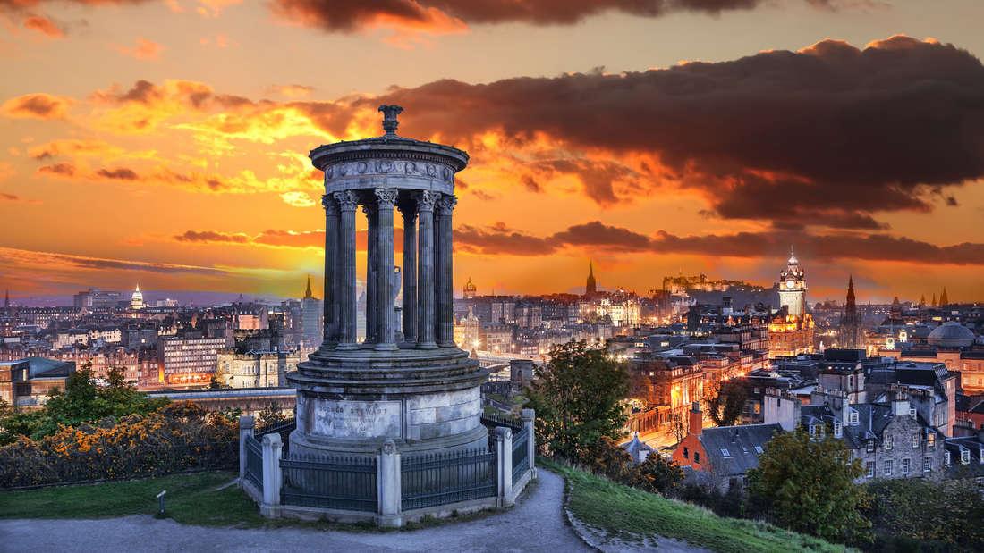 Eine Aussicht auf Edinburgh mit Calton Hill in Schottland bei Sonnenuntergang.