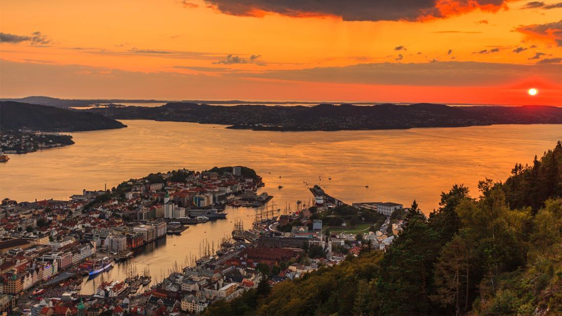 Eine Aussicht über die norwegische Stadt Bergen vom Berg aus. Es sind viele Häuser, ein Hafen, viel Wasser und Berge bei Sonnenuntergang zu sehen.