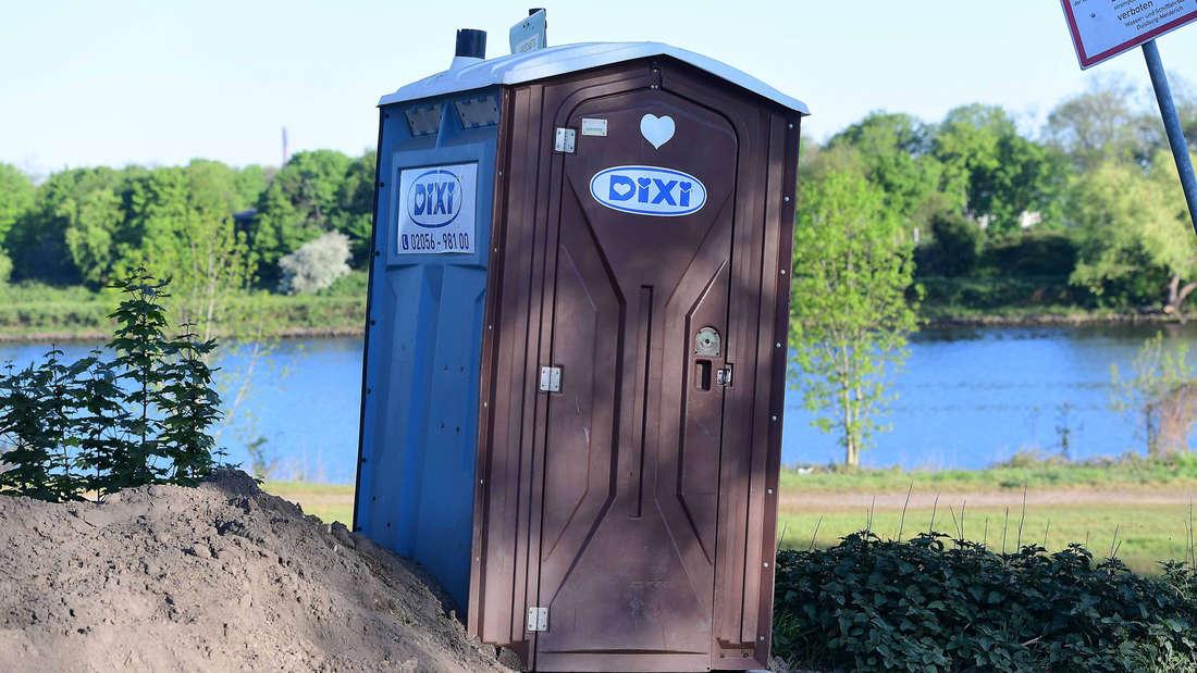 Eine mobile Dixi-Toilette, die auf einem Stück Wiese zwischen einem Sandberg und Blättern steht.