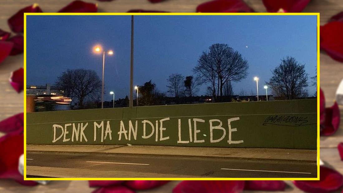 """An eine Wand neben einer Straße wurde: """"Denk ma an die Liebe"""" gesprüht."""
