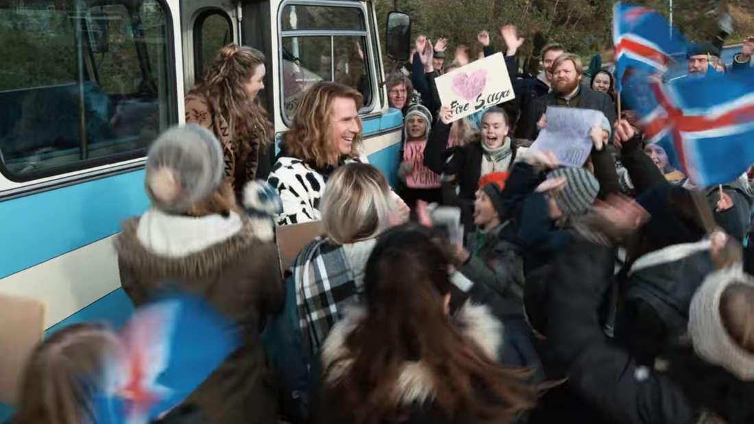 Fire Saga steigt aus dem Bus und wird von Fans, Island-Flaggen und Plakaten in Empfang genommen.