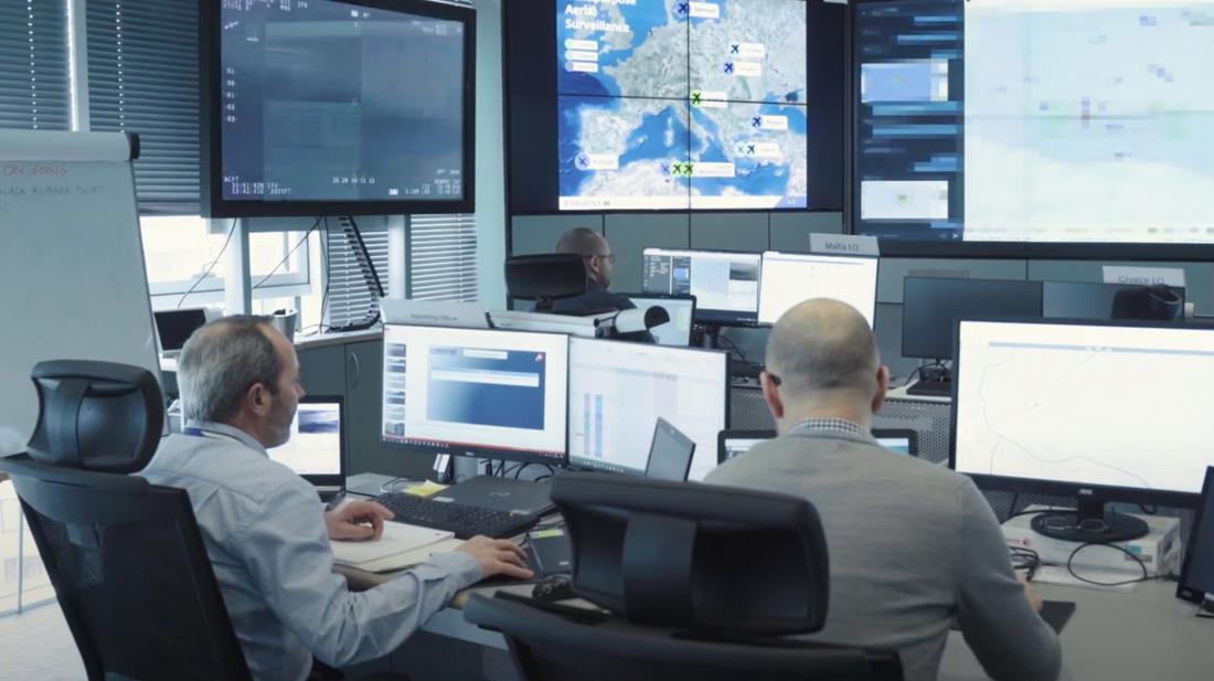 Männer schauen auf Bildschirme im Frontex Hauptquartier