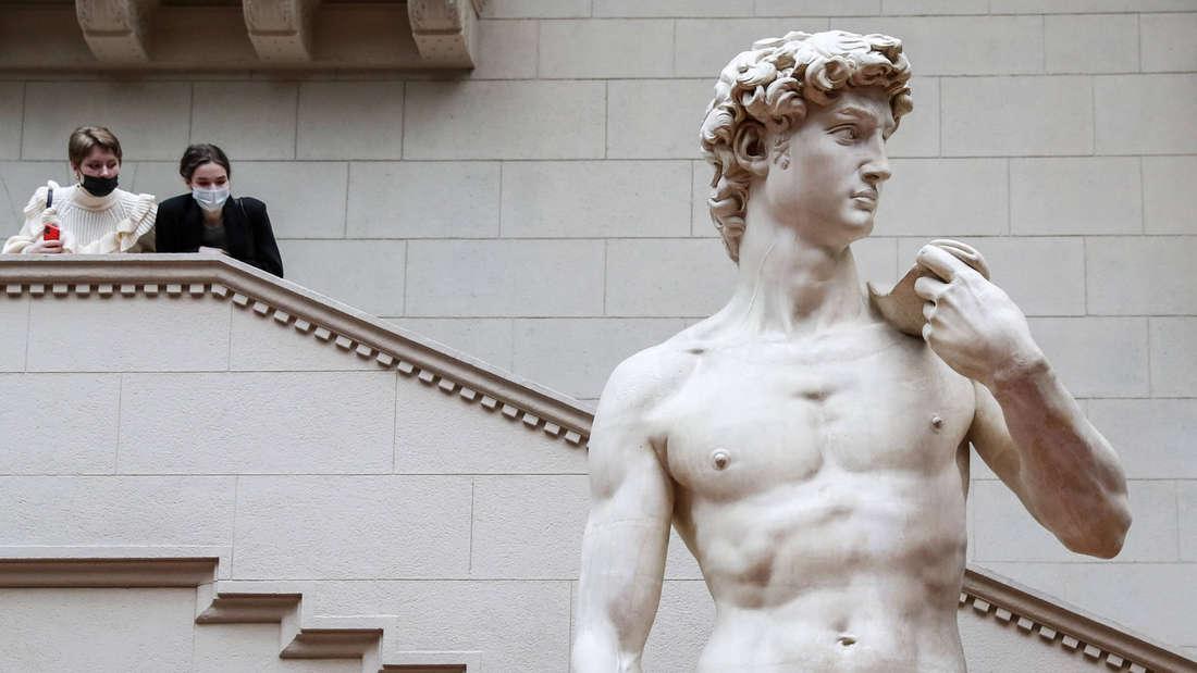 Zwei Personen mit Maske, die von einer Treppe aus auf die David-Statue von Michelangelo herunterschauen.