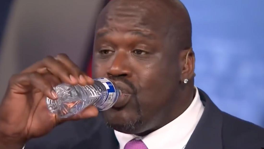 Shaquille O'Neal trinkt aus einer normalgroßen Wasserflasche, die in seiner Hand sehr klein aussieht.