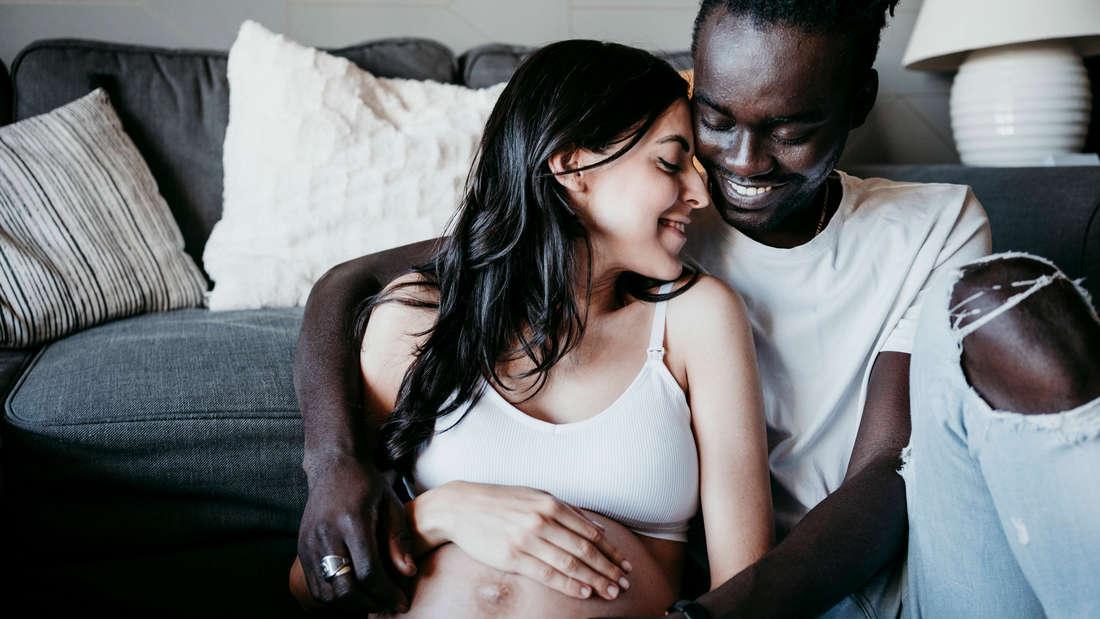 Ein Mann, der seine schwangere Frau festhält. Beide sehen sehr glücklich aus.