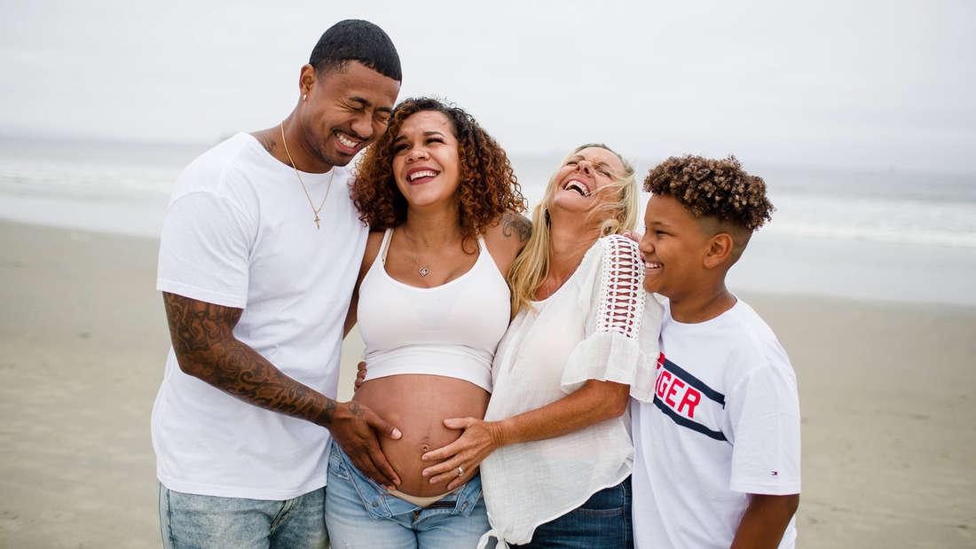 Ein Schwarzer Mann und eine ältere Frau, die ihre Hand auf den Babybauch einer Schwarzen Frau gelegt haben. Daneben ein Schwarzer Junge, der lächelt. Alle zusammen stehen am Strand und sehen sehr glücklich aus.