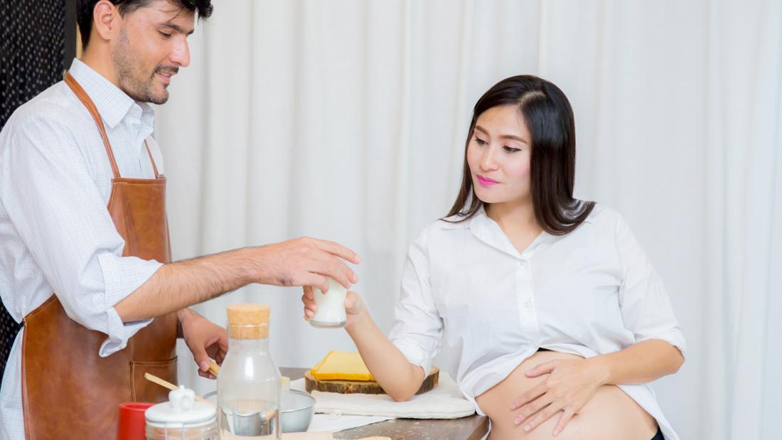 Ein Mann, der einer schwangeren asiatischen Frau ein Glas Wasser reicht. Die Frau hat ihre Hand auf ihren Babybauch gelegt und nimmt das Glas an.