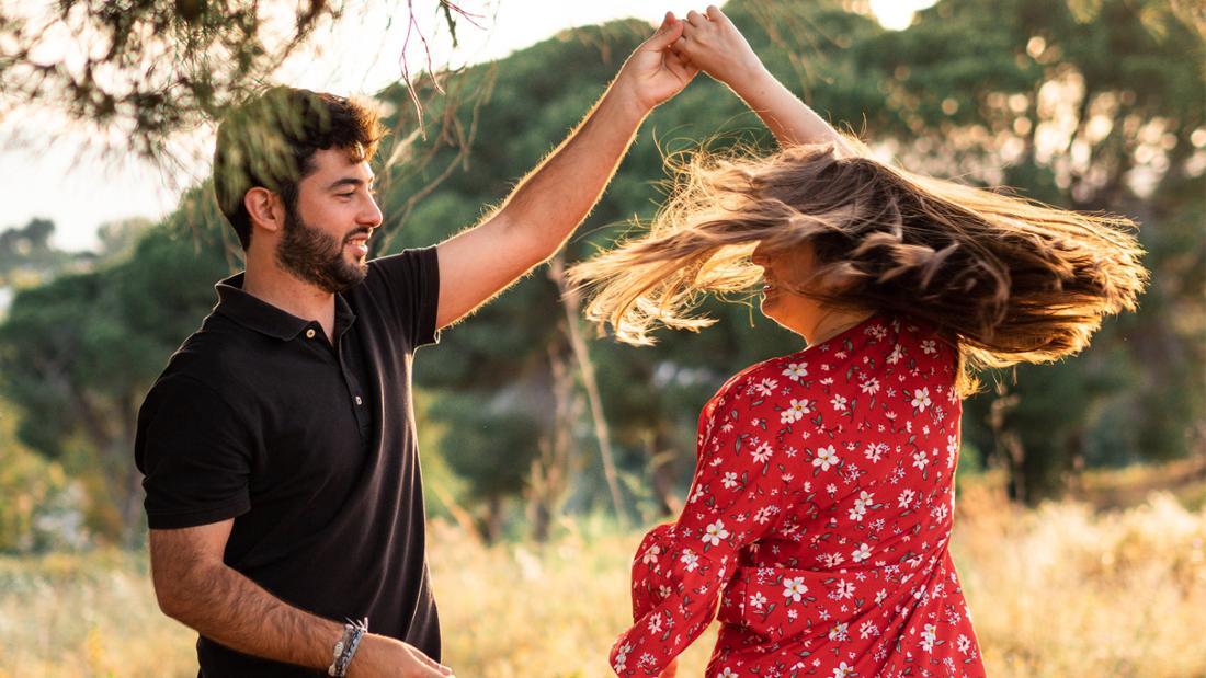 Ein Mann, der seine schwangere Frau beim Tanzen dreht. Die Frau lächelt, ihre langen Haare fliegen im Wind und ihr rotes Kleid dreht sich mit ihr.