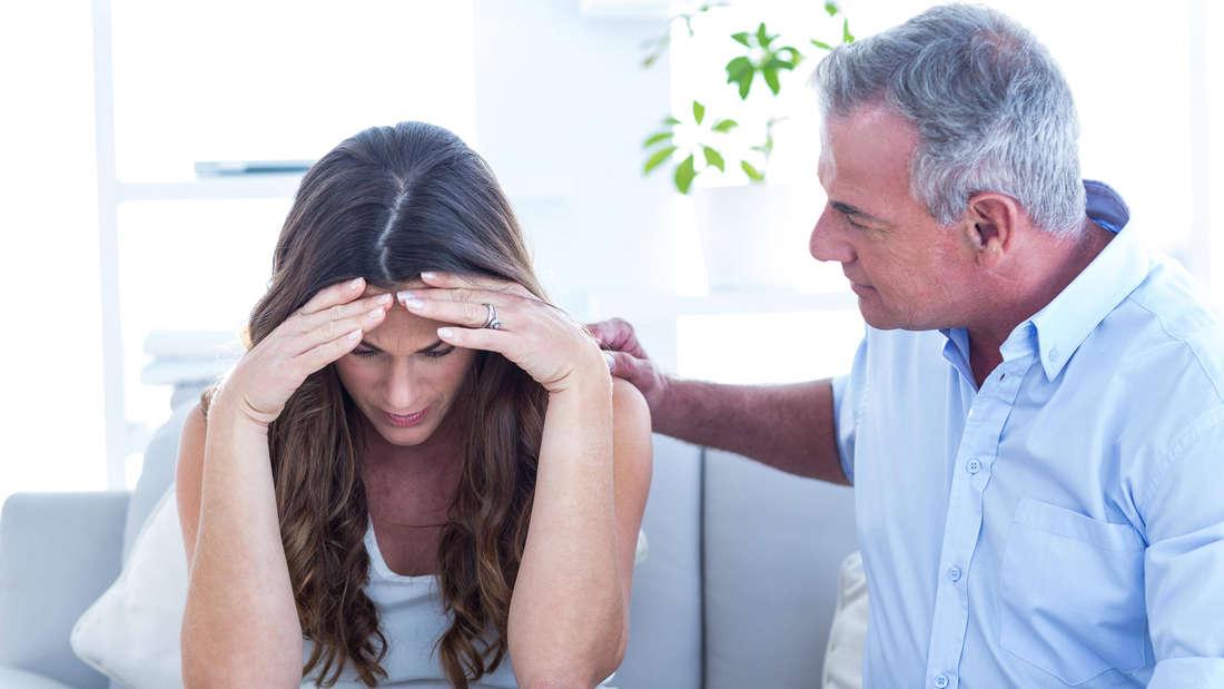 Ein Mann, der seine schwangere Frau tröstet und ihr die Hand auf die Schulter legt, während sie verzweifelt aussieht.