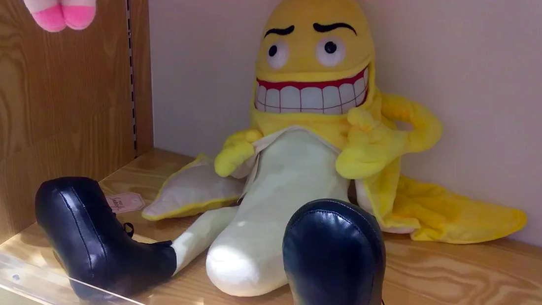 Eine Plüsch-Banane mit Gesicht schält breit grinsend ihre untere Hälfte