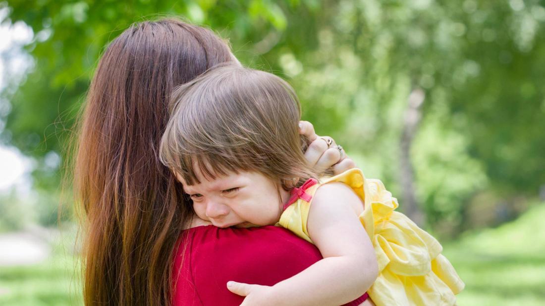 Eine Mutter, die ein weinendes Mädchen auf dem Arm hält
