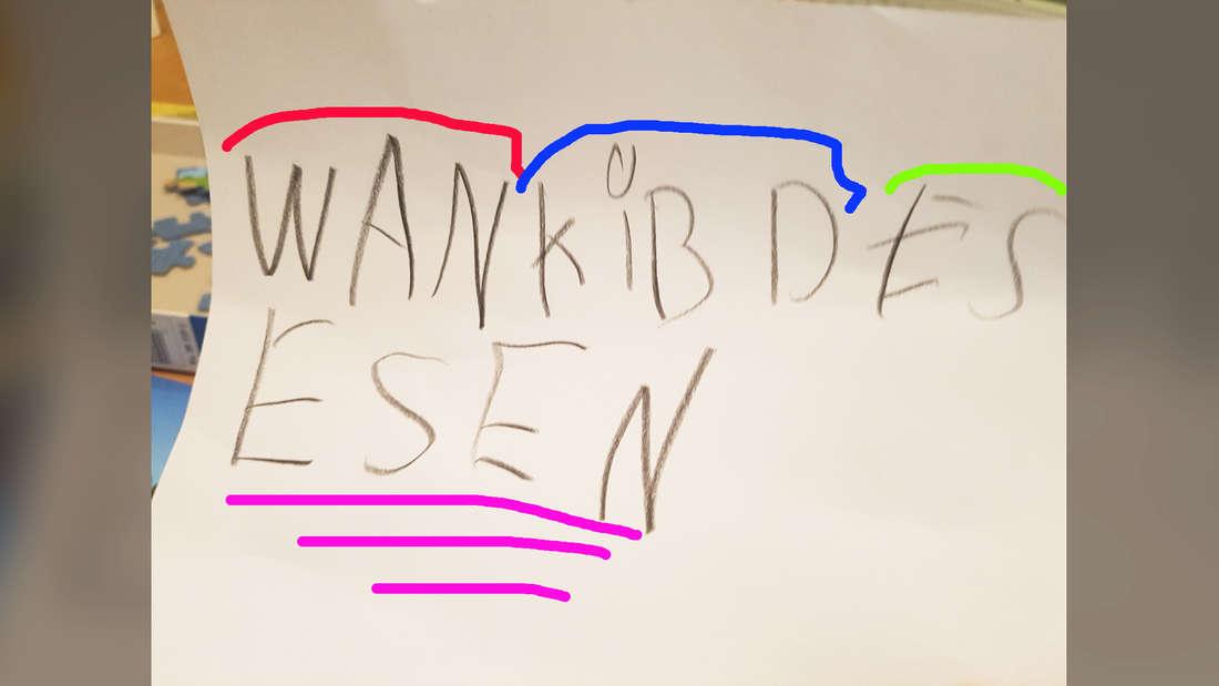 """Ein Bild von einem Kind, auf dem in gemalten Buchstaben und jeweils farblich abgetrennt """"WAN KIB D ES ESEN"""" steht. """"ESEN"""" ist mit lila drei Mal unterstrichen."""