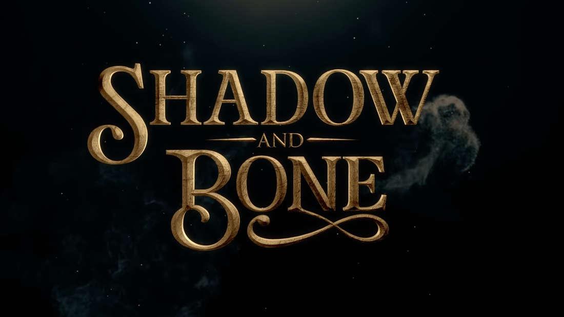 """Der goldene """"Shadow and Bone"""" Schriftzug auf einem schwarzen Nachthimmel."""