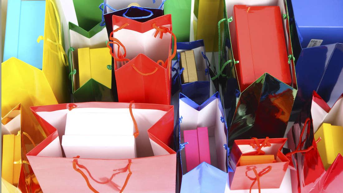 Viele bunte Geschenktüten in blau, rot, gelb und grün, in denen jeweils Geschenke liegen.