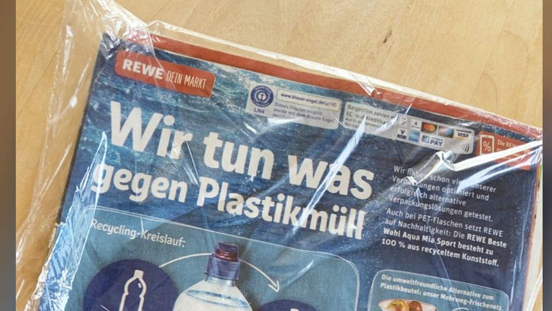 """Ein eingeschweißter Rewe-Prospekt, auf dem drauf steht """"Wir tun was gegen Plastik""""."""