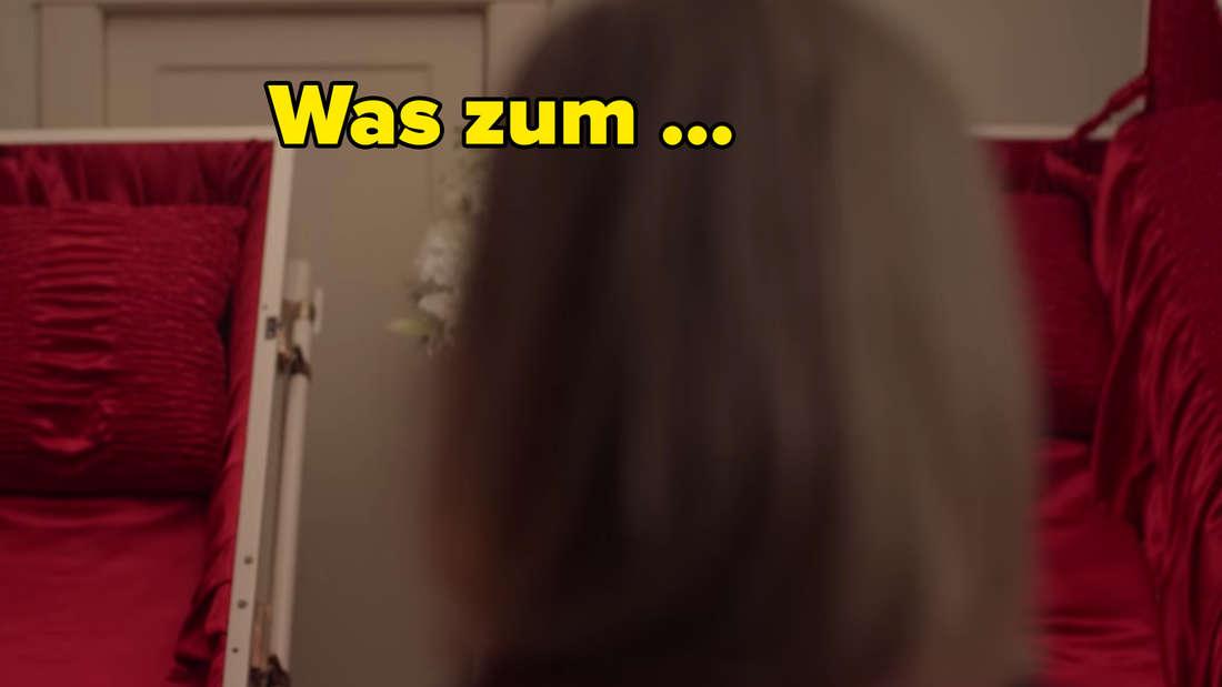 Eine Frau steht vor zwei offenen Särgen in ihrem Schlafzimmer.
