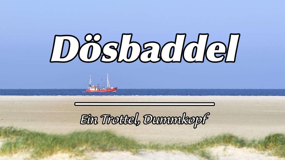 """Ein roter Fischkutter am Strand von Sankt Peter-Ording. Auf dem Bild steht """"Dösbaddel"""" und als Erklärung """"Ein Trottel, Dummkopf."""""""