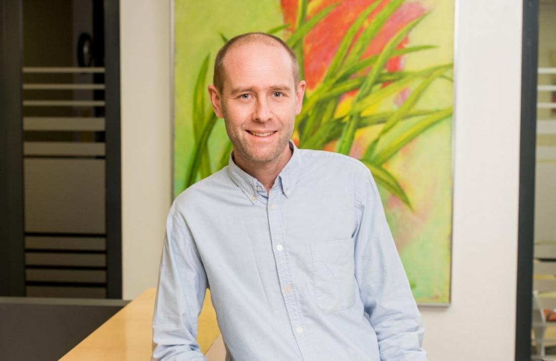 Niklas Schurig steht in Hemd vor einem Bild.