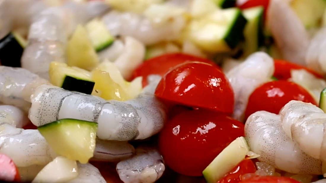 Halbierte Cherrytomaten und frische Garnelen werden im Wok mit dem angebratenen Gemüse vermischt
