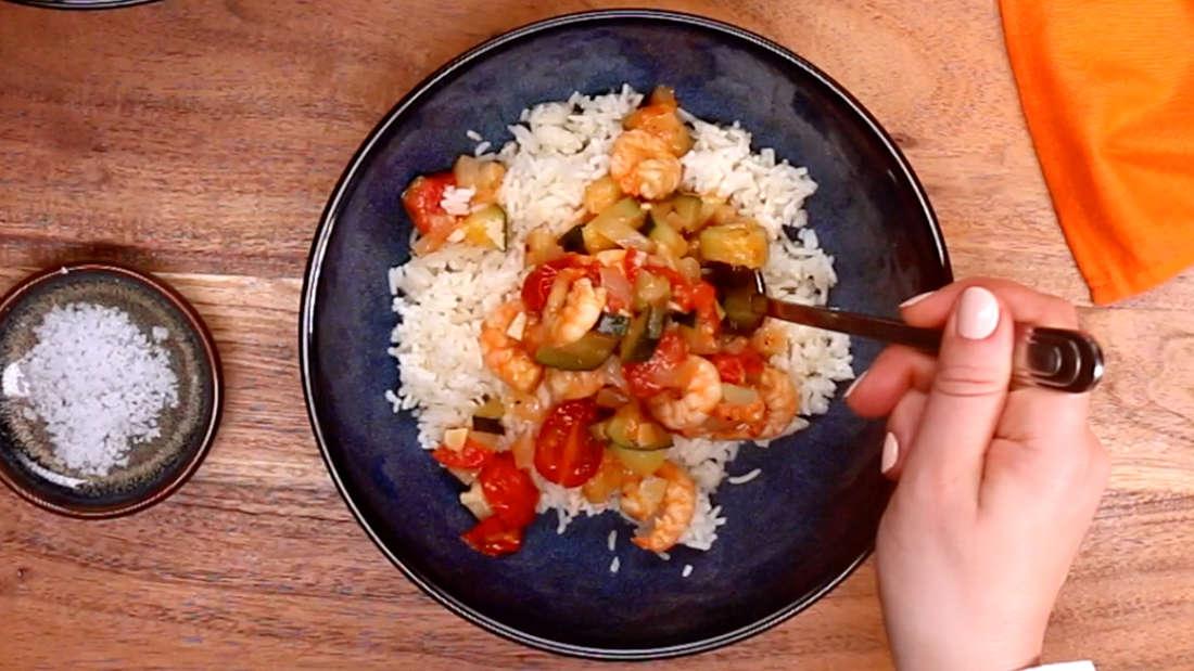 Eine weibliche Hand führt die Gabel zur Schüssel mit dem Garnelen-Basmati-Reis Gericht