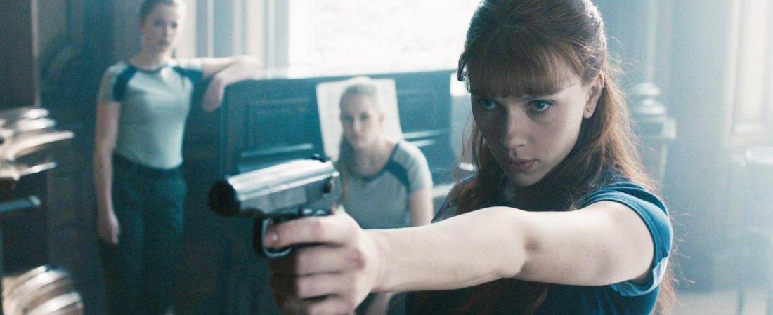 Black Widow hält mit konzentriertem Gesichtsausdruck eine Waffe ausgestreckt. Hinter ihr ihm Raum befinden sich zwei weitere junge Frauen.