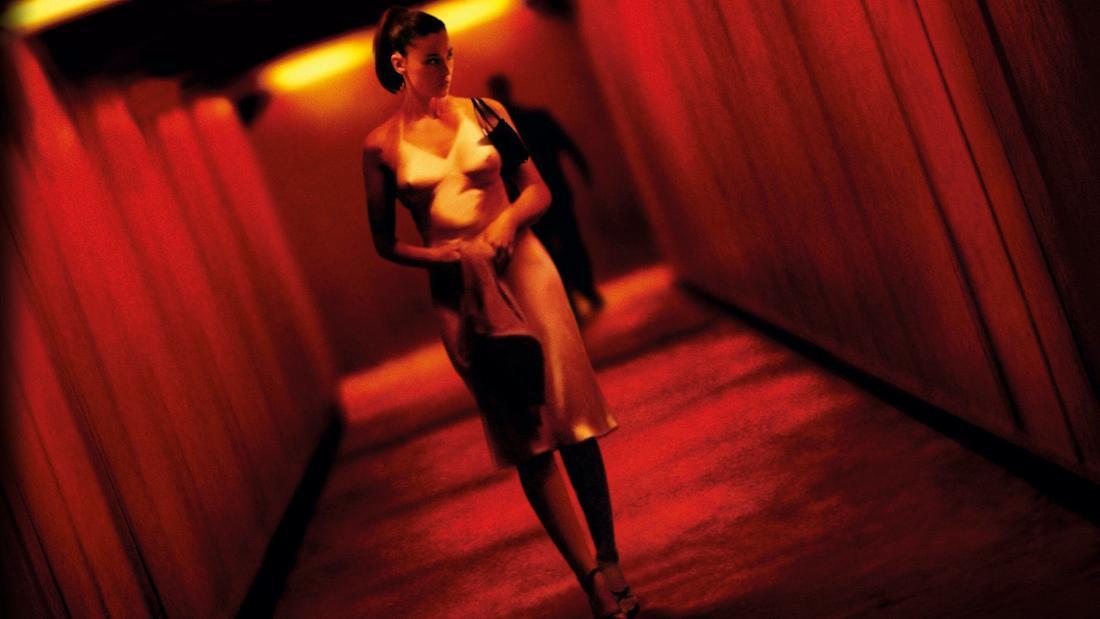 Eine junge Frau geht durch einen rötlich beleuchtenden Tunnel. Im Schatten läuft hinter ihr eine Gestalt.