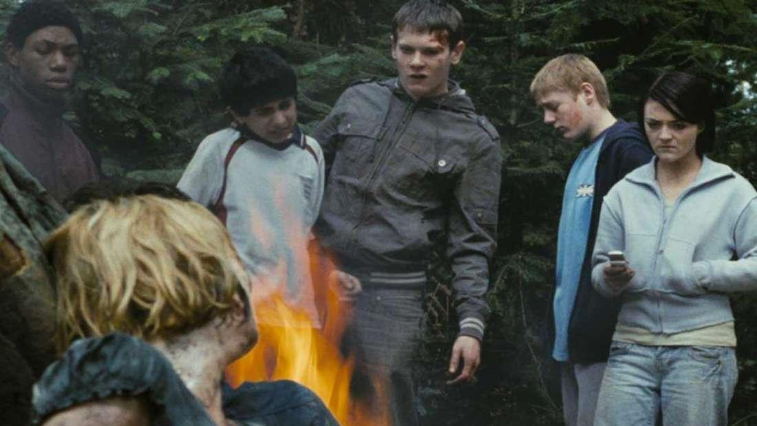Eine Frau ist an einen Baumstupf gefesselt. Hinter ihr brennt ein Feuer, vor dem eine Gruppe Jugendlicher steht.