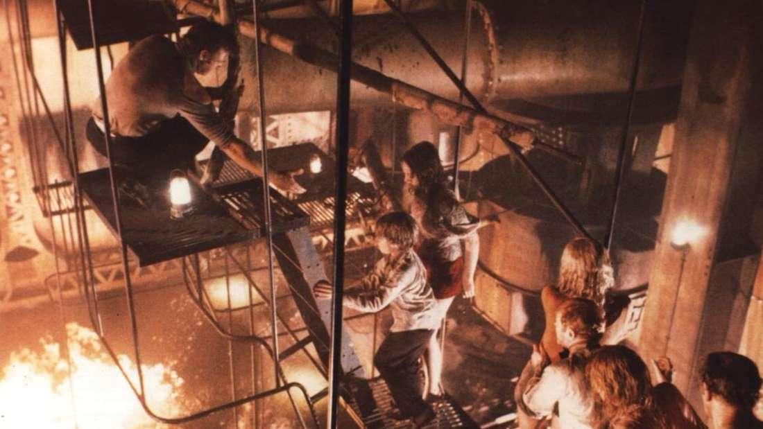Eine Gruppe Menschen kämpft sich den Weg durch ein Inferno im Maschinenraum eines Schiffes