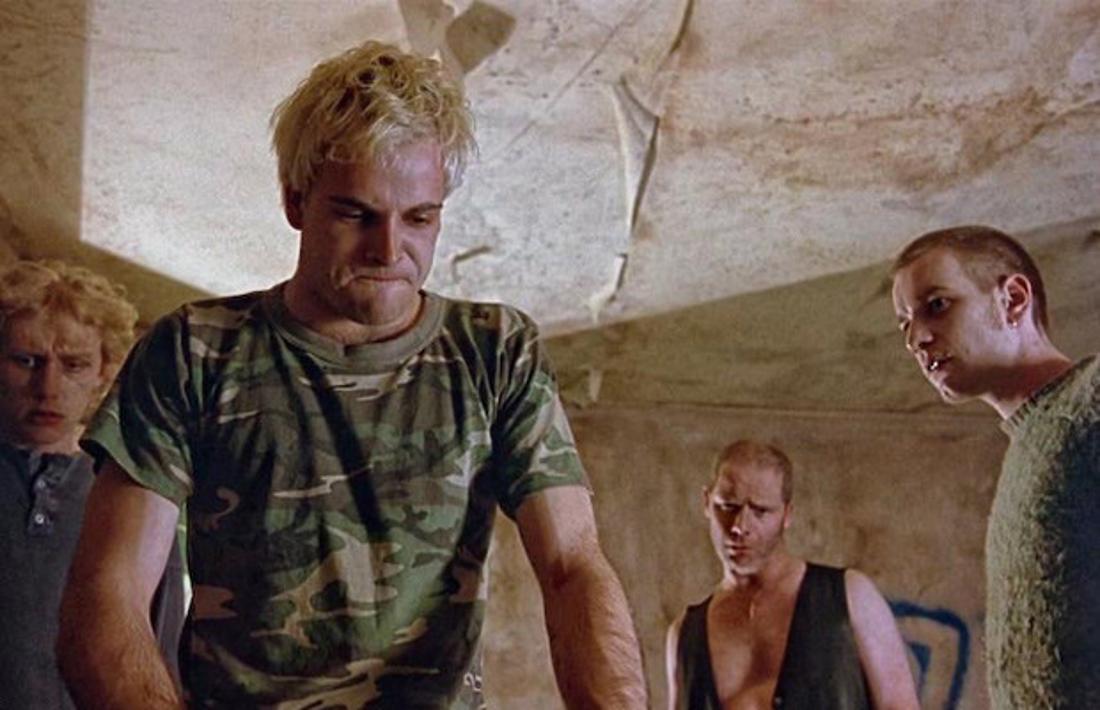 Jonny Lee Miller, Ewan McGregor und zwei weitere Darsteller in Trainspotting starren auf etwas in ihrer heruntergekommenen Wohnung hinunter