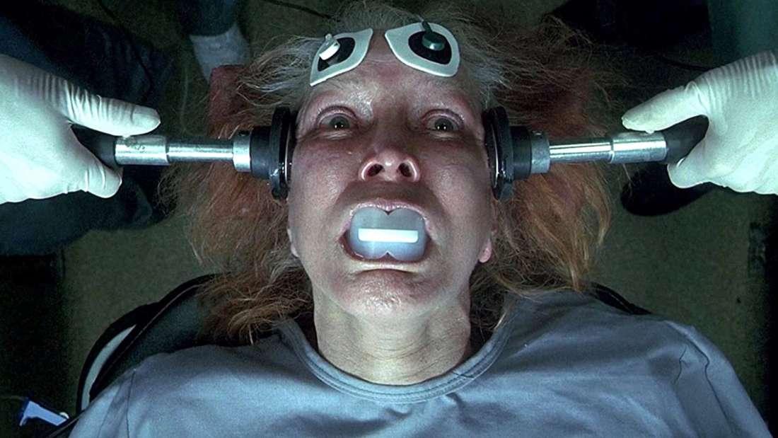 """Ellen Burstyn in """"Requiem for a Dream"""" liegt zu einer Elektroschockbehandlung auf einem Tisch. Ihre rot-grauen Haare stehen zu Berge und ihre Augen sind weit aufgerissen."""