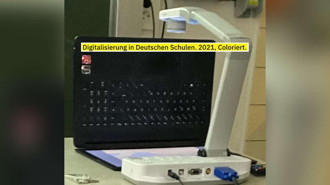 Ein Laptop, der so unter einen Projektor gelegt wurde, dass das Bild auf dem Laptop an die Wand projiziert werden kann.