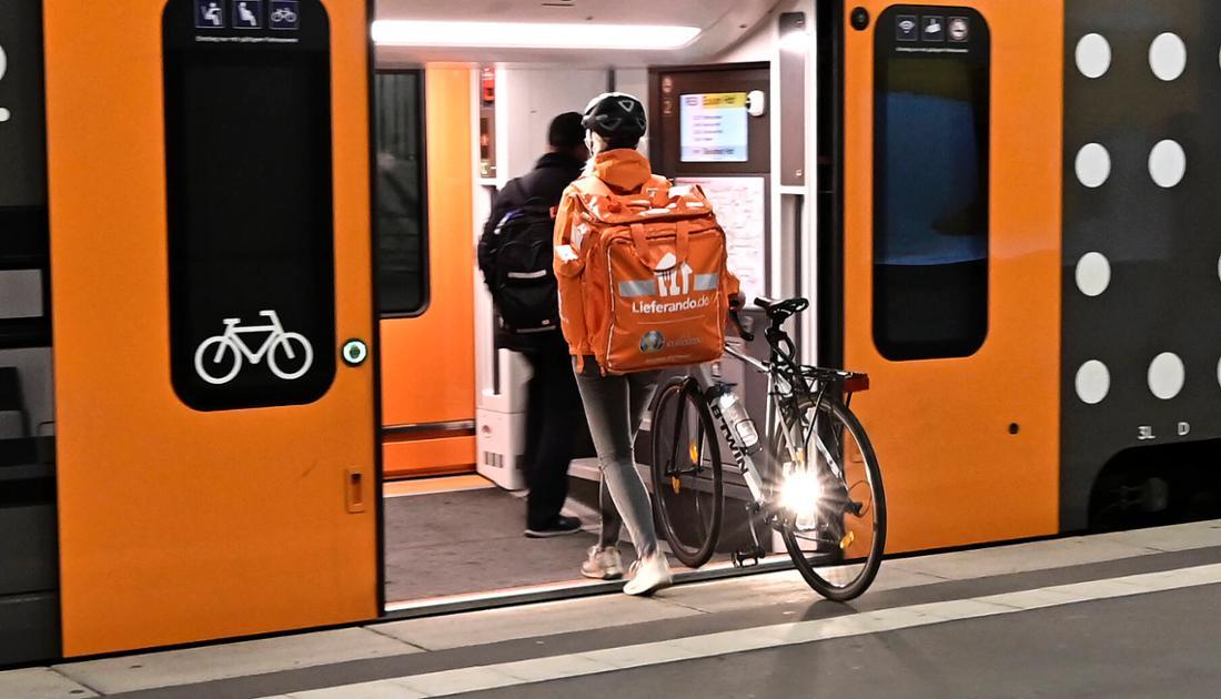 Eine Lieferando-Kurierin schiebt ihr Rad in eine U-Bahn.