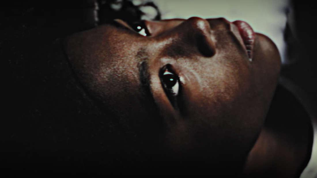 Ein totes Mädchen liegt mit offenen Augen da. Auf ihre Stirn ist eine Linie aufgemalt.