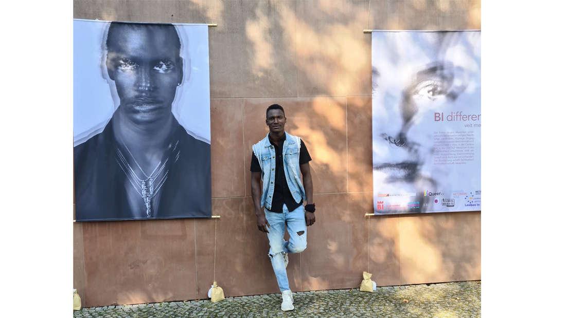 Sekou Yatara alias Remy, der neben zwei Plakaten steht und lächelt.