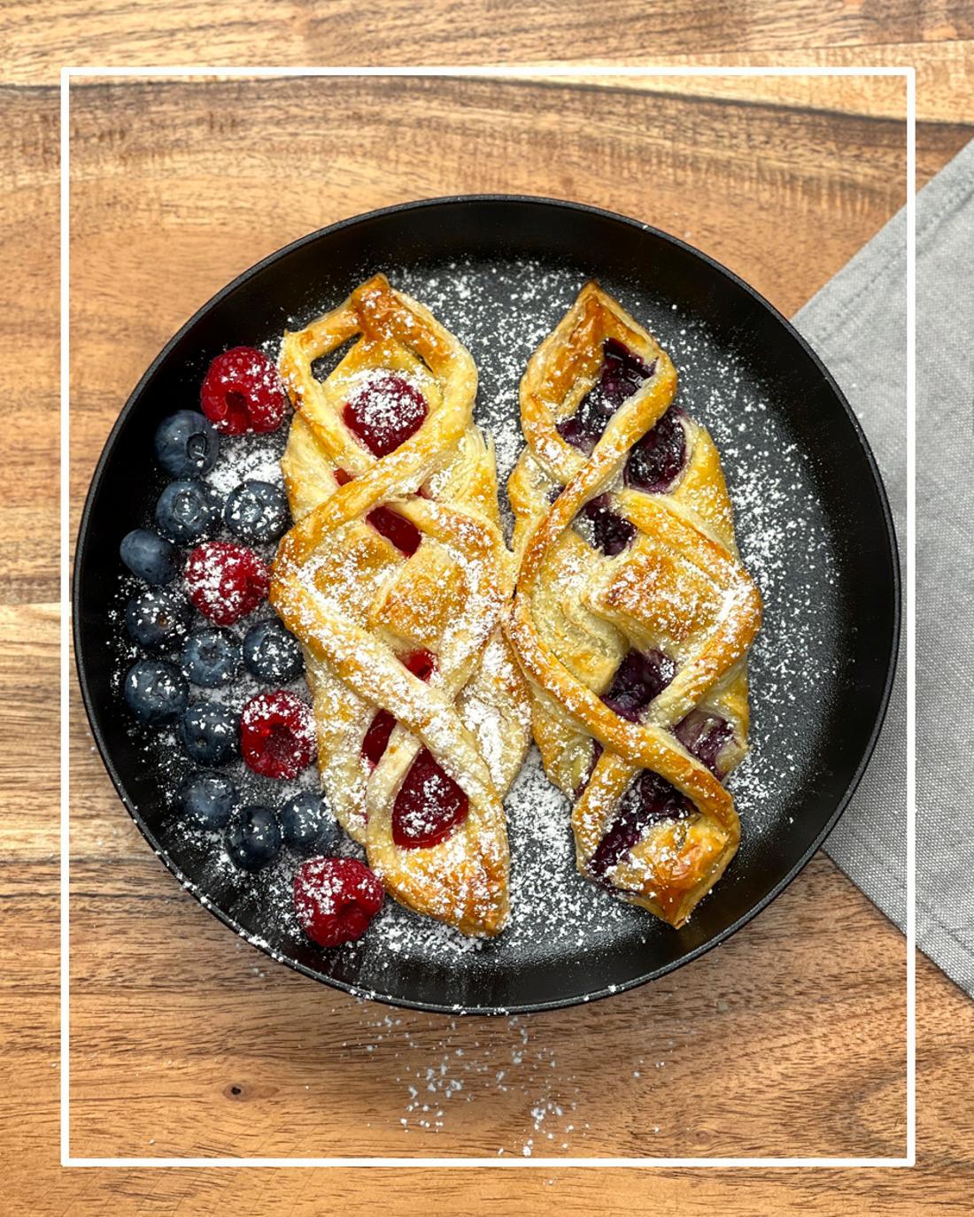 Ein Teller, auf dem zwei Blätterteigzöpfe mit Beeren liegen. Über diese ist Puderzucker gestreut.