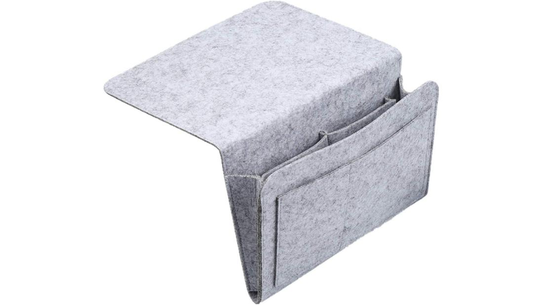 Hellgraue Bettasche aus Filz, mit mehreren Fächern und Lasche zum Einhängen.