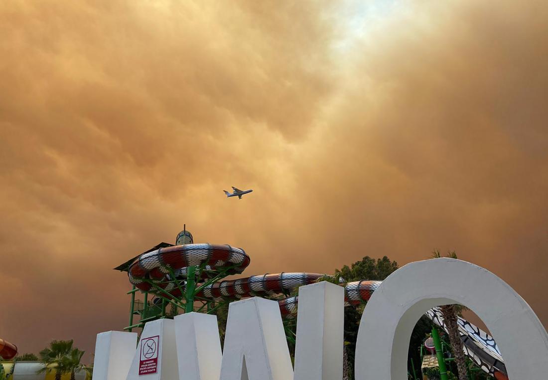 Rauch zieht über die Freizeitanlagen an einem Hotelkomplex in der türkischen Urlaubsregion Antalya, während sich ein Flugzeug im Landeanflug befindet. Winde trieben die Flammen mehrerer Waldbrände in Richtung der Wohnbezirke, wie der Landrat des Bezirks Manavgat dem Sender CNN Türk sagte.